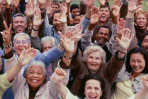 Large group of people smiling with their hands in the air.