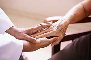 A closeup of a younger person holding an older person's hand.